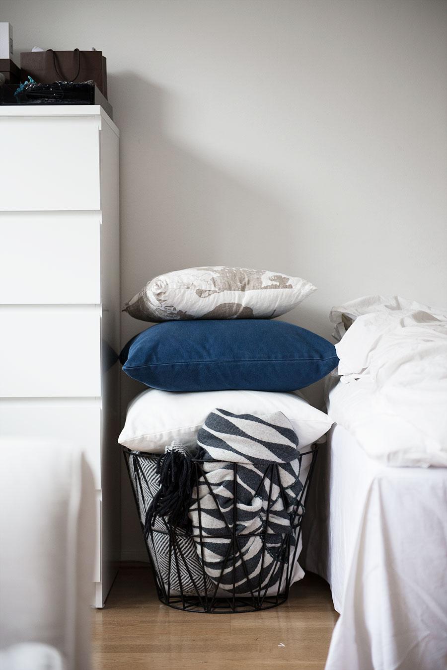 Smart förvaring av extra kuddar och filtar i en korg från Ferm Living.