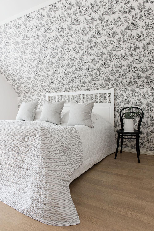 Sovrum med mönstrad tapet.