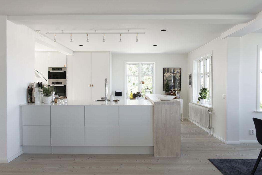 Under renoveringen blev köket dubbelt så stort. Paret ville undvika att placera hela köket längs med väggarna och planerade därför istället in en stor köksö. Med hjälp av dubbla underskåp rygg i rygg skapades bra plats för förvaring och dessutom en extra stor bänkyta att duka upp härliga bufféer på. Vita köksluckor och bänkskiva från HTH. Vit bänkskiva i hårdkomposit, träbänkskiva av vitlaserad ask. De bruna läderhandtagen har Frida specialdesignat hos Sadelmakarmästarna i Stockholm. Taklampa Star från Jonas Bohlin. Ugn och ångugn är från märket Miele. Blandare från FM Mattsson.