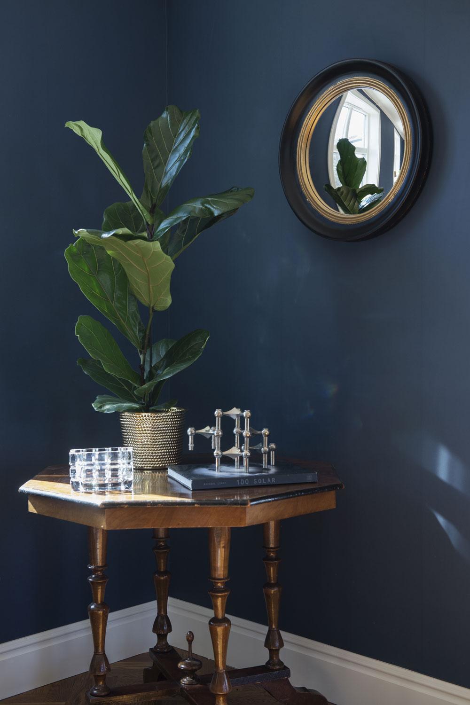 Det octagonformade hörnbordet är antikt. Den runda väggspegeln kommer från Butik Victoria. Nagelljusstaken har Therese fyndat på loppis. Mässingskruka från Svenskt tenn, kristallvas från Orrefors.
